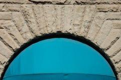 Arco de la pared de piedra con el toldo azul en Portland, O Foto de archivo