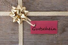 Arco de oro con la etiqueta roja con Gutschein Imágenes de archivo libres de regalías
