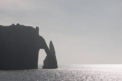 Arco de piedra en la costa de Normandía en calina imágenes de archivo libres de regalías