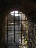 Arco de piedra viejo con la puerta de la rejilla del hierro imagen de archivo libre de regalías