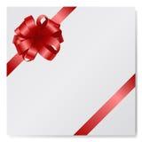 Arco de seda rojo en la tarjeta de papel vacía aislada en el blanco Foto de archivo