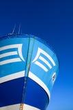 Arco del azul y blanco de un barco rastreador en un cielo azul Imagen de archivo