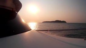Arco del barco en el fondo de una puesta del sol hermosa en el mar metrajes