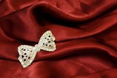 Arco del gioiello su seta rossa Fotografie Stock Libere da Diritti