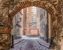 Arco del mattone rosso con una strada cobbled fotografie stock libere da diritti