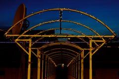 Arco del metal entrelazado con una guirnalda con las luces LED en la noche manera en perspectiva fotos de archivo