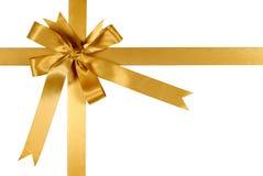 Arco del nastro del regalo dell'oro giallo isolato su fondo bianco Fotografia Stock