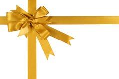 Arco del nastro del regalo dell'oro giallo isolato su fondo bianco Immagini Stock