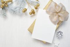 Arco del oro del regalo de la Navidad de la maqueta y cono del árbol, flatlay en un fondo de madera blanco, con el lugar para su  foto de archivo libre de regalías