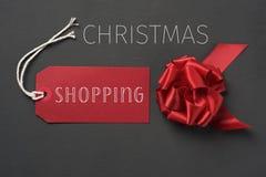 Arco del regalo y el hacer compras rojos de los chrismtas del texto Fotografía de archivo