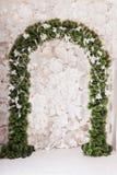 Arco dell'albero di Natale intrecciato con i rami e le foglie congelati Fotografie Stock