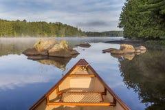 Arco della canoa su un lago nel primo mattino - Ontario, Canada immagini stock libere da diritti
