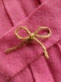 Arco della cordicella su cashmere rosa fotografia stock libera da diritti