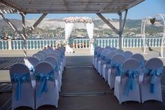Arco di cerimonia di nozze, altare decorato con i fiori sul prato inglese Mare e montagne a fondo Immagini Stock Libere da Diritti