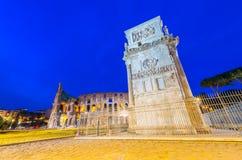 Arco di Costantino och Colosseo på natten - Costantines båge nära Royaltyfria Bilder