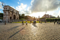 Arco di Costantino Roma. Rome, Italy - May 12, 2016: People and tourists walking in front of the Arch of Constantine spectacular at sunset, located between the Stock Photos