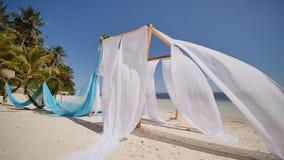 Arco di nozze decorato con i fiori sulla spiaggia vicino all'oceano Le sue tele bianche e blu volano nel vento decorativo stock footage