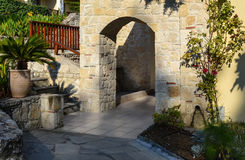 Arco di pietra ed arbusti verdi Immagine Stock