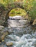 Arco di pietra sopra il flusso scorrente veloce Immagine Stock