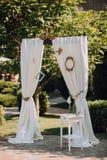 Arco do casamento decorado com as cortinas brancas de pano, o quadro e o meio-fio branco com garrafas imagem de stock royalty free