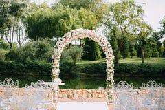 Arco do casamento decorado com as rosas das flores, as brancas e as cor-de-rosa Com cadeiras do vintage em um fundo da lagoa no v fotografia de stock royalty free