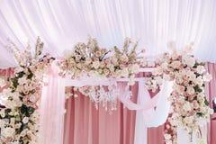 Arco do casamento decorado com o pano branco e cor-de-rosa, o candelabro de cristal e composições florais bonitas das rosas e do  fotos de stock royalty free