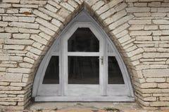 Arco do triângulo na parede de pedra com porta e Windows Imagens de Stock