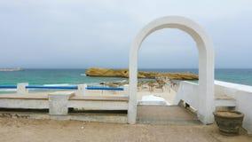 Arco e cerca brancos na praia com guarda-chuvas e rochas perto do mar filme