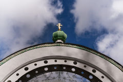 Arco e Green Dome com uma cruz dourada no céu azul entre Fotos de Stock