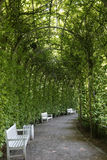 Arco em um parque com bancos brancos Fotografia de Stock Royalty Free