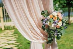Arco hermoso de la boda, adornado con el paño del biege y las flores, primer Fotografía de archivo