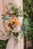 Arco hermoso de la boda adornado con el paño y las flores amelocotonados Fotos de archivo
