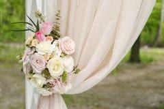Arco hermoso de la boda adornado con el paño y las flores beige Imágenes de archivo libres de regalías