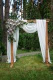 Arco hermoso de la boda adornado con las flores en el parque Imagenes de archivo