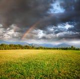 Arco iris bajo campo de hierba Imagenes de archivo