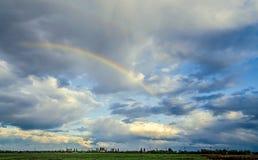 Arco iris coloreados sobre el cielo azul, día lluvioso Imagenes de archivo