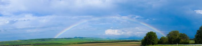 Arco iris con las nubes sobre campo de granja Imagenes de archivo