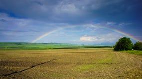 Arco iris con las nubes sobre campo de granja Foto de archivo libre de regalías