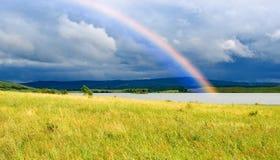 Arco iris de los colores sobre el lago y campos Imagen de archivo