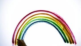 Arco iris del color de dibujo hecho de la arena en la pantalla brillantemente encendida