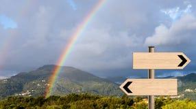 Arco iris del paisaje con los postes indicadores Metáfora de la dirección de la vida Foto de archivo