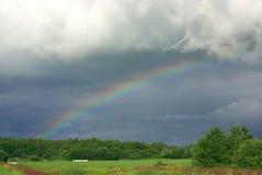 Arco iris delante de las nubes de una lluvia de la obscuridad Imagen de archivo