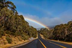 Arco iris doble sobre el camino y el bosque de la montaña Foto de archivo libre de regalías