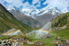 Arco iris en canalones de agua de irrigación en montaña de las montañas del verano Fotos de archivo libres de regalías