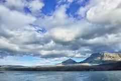 Arco iris en el cielo nublado sobre las montañas cerca del lago Imágenes de archivo libres de regalías