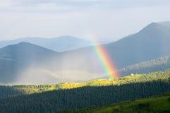 Arco iris en las montañas sobre las casas Fotos de archivo libres de regalías