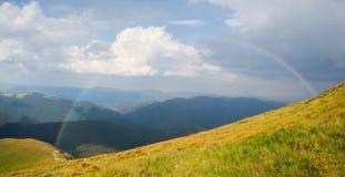 Arco iris grande en las montañas Imagen de archivo libre de regalías