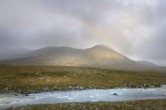 Arco iris que forma en las nubes de lluvia en luz del sol de oro del paisaje del verde del otoño en las montañas Foto de archivo