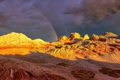 Arco iris sobre el bolsillo blanco de la meseta durante puesta del sol