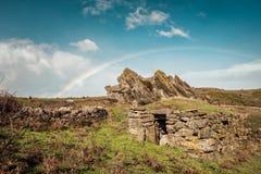 Arco iris sobre el edificio de piedra antiguo en las montañas de Córcega fotos de archivo